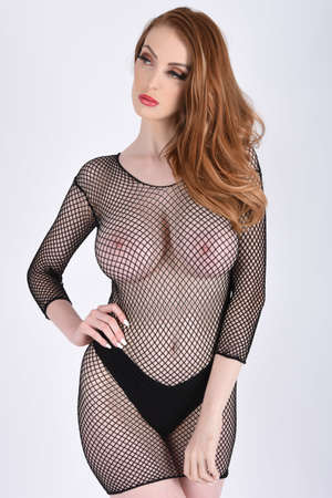 Beautiful, tall, redhead model dressed in a black mesh bodysuit,isolated against a white background