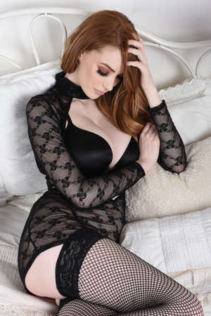 Attractive, tall, slim, redhead model dressed in a black lace dress and lingerie, lying on her bed