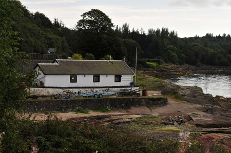 slipway: Boat shed at the side of the river Clyde near Inverkip. Stock Photo