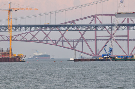 trafic: Construction of the new Forth Road Bridge taken from the south shore, with the original road bridge and the rail bridge in the background.