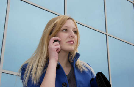 Business lady with a cell phone with a building behind