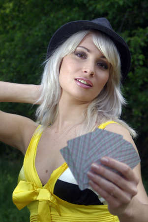 Bleached blonde in a country hat with cards Editorial