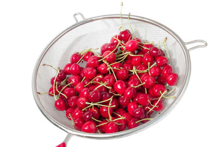 Red cherry berry in a net colander. Isolated.