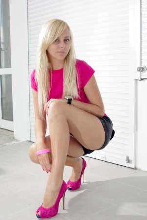 Blonde squatting on the white empty street photo