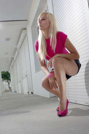 Blonde squatting on the white empty street Stock Photo