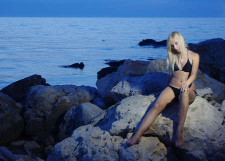 Blonde beach girl near the water on rock