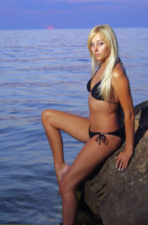 Blonde beach girl with tender look near the water on rock before setting sun