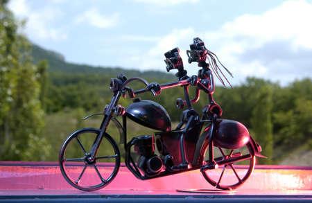 Welded steel biker and a female on a bike                    Stock Photo