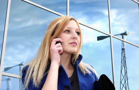 Blonde business lady with cell phone on office building reflecting windgenerators and clouded sky