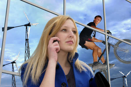 Blonde business lady with cell phone on office building reflecting windgenerators and clouded sky with hopping rider