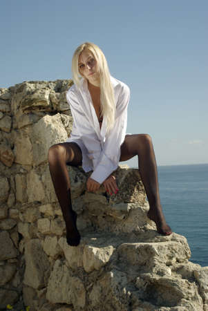 Bleacned blonde in a white shirt and black stockings sitting on an ancient wall near open sea