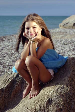 klein meisje op strand: Klein meisje in een zons ondergang licht zittend op een rots op een strand Stockfoto