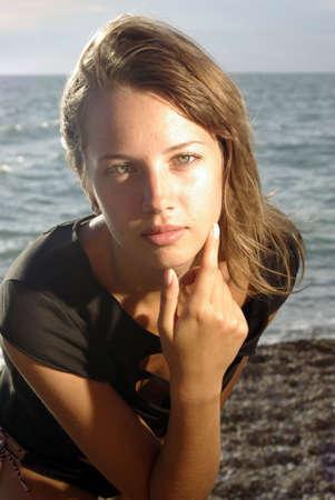 onbepaalde: Portret van de jonge dame op een strand, close-up gezicht hand en schouders Stockfoto