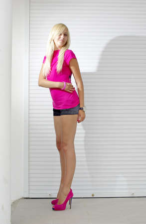 Blonde in pink shirt and high heel shoes standing on white street photo