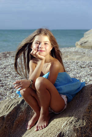 Little girl in a sunset light sitting on a rock on a beach Stock Photo - 8577116