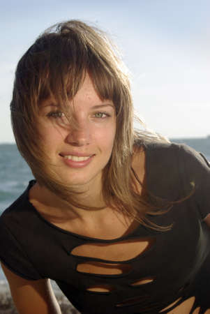 smiling lady portrait on a beach, close up face hand and shoulders photo