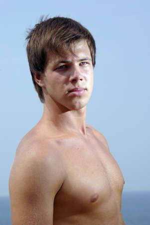 nackte brust: Happy guy bare chest near sea beach. Lizenzfreie Bilder