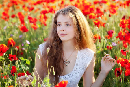 red poppies on green field: girl on a red poppy field