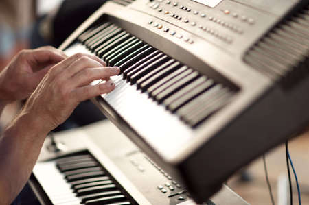 musician hands on keyboards playing