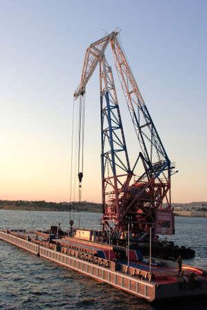 sea crane near pontoon in sunset light Stock Photo