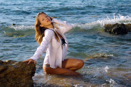 girl in a wet white shirt kneeling in a foaming surf near rock, mouth open photo