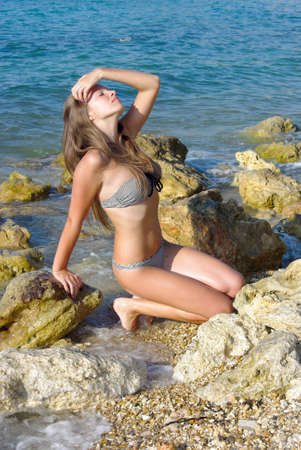 girl touches hair on a rocky beach Stock Photo