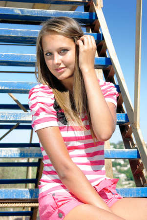 young smiling beauty sits on a ladder over sky Stock Photo