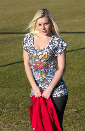 young lady on a football field with a red jacket Stock Photo