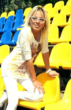tribune: girl in glasses on empty stadium tribune Stock Photo