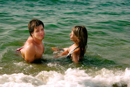girl and boy on a sandy beach in the water Stock Photo