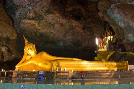 eyes cave: Golden statue of reclining buddha in Suwrrncoha cave temple in Phangnga, Thailand