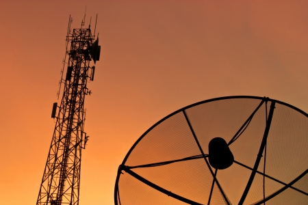 Satellite dish and communication tower at sunset