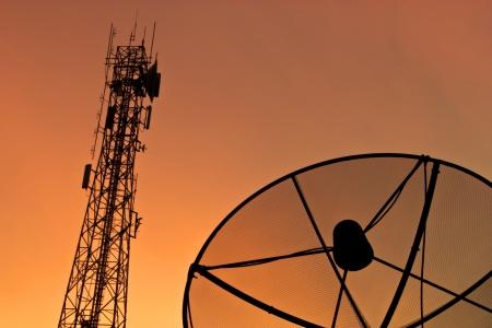 Satellite dish and communication tower at sunset