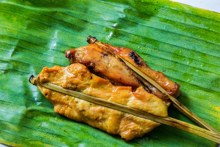 Roasting chicken on a banana leaf photo
