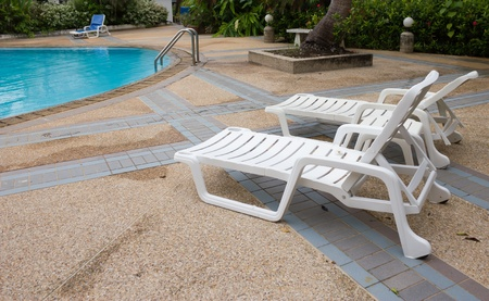teck: Long chairs set by swimming pool