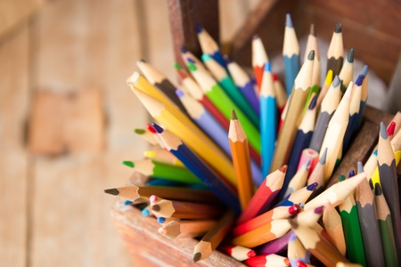 Colored pencils in wooden crates photo