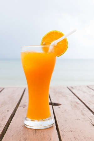 Glass of orange juice on a beach table photo