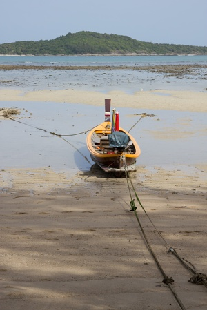 Wooden fishing boat on the beach in Thailand photo