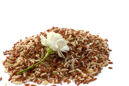 unpolished: Unpolished red rice with jasmine flower isolated on white background Stock Photo