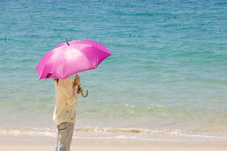 umbella: Woman with umbella on the beach Stock Photo