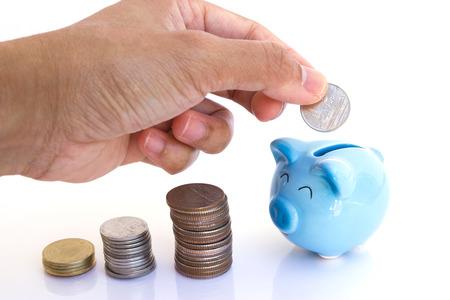 Drops money into the piggy bank photo