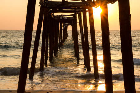 Decaying wooden bridge in the sea with sunset photo