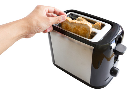 Hand pick bread from toaster Stock Photo