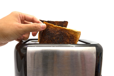 burnt toast: Hand taking burnt toast out of toaster