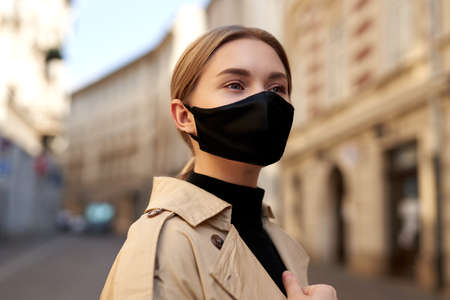 Woman wearing trendy fashion outfit during quarantine of coronavirus outbreak. Model dressed protective stylish handmade face mask. Tourist walkin on empty street. Beautiful blonde woman with fashion protective mask. Architecture background. Street Zdjęcie Seryjne
