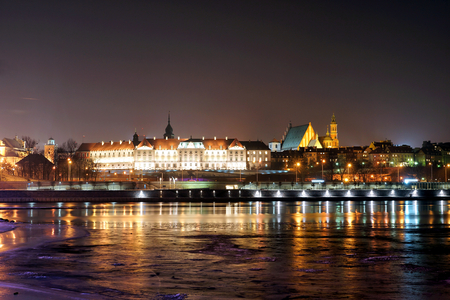 Night view of the Royal Castle and Vistula river in Warsaw, Poland