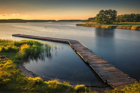 Footbridge on Lake Kirsajty during the sunset, Masuria, Poland Stockfoto - 130068124