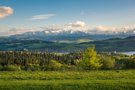 Panorama of snowy Tatra mountains and castle in Czorsztyn during spring sunset, Malopolskie, Poland