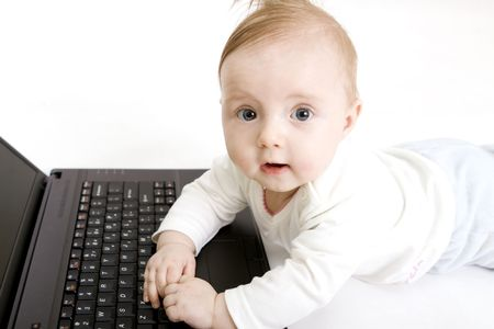 Little baby with laptop on white photo