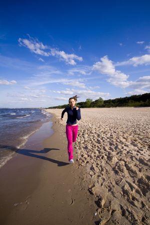 Active woman running on the beach photo